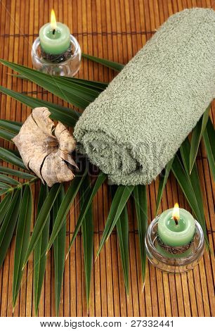 Towel, candles and palm frond