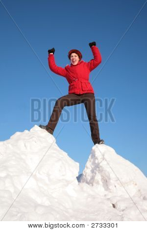 Woman In Red Jacket On Top Of Snow Hill