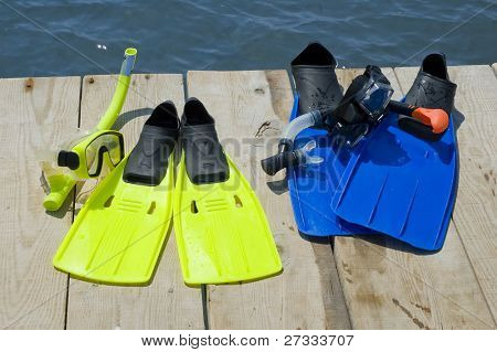 Colorful flippers on a pier near the ocean
