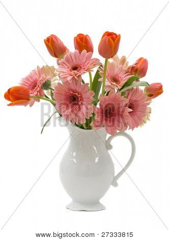 A bouquet of daisy gerberas and tulips in a beautiful pitcher vase