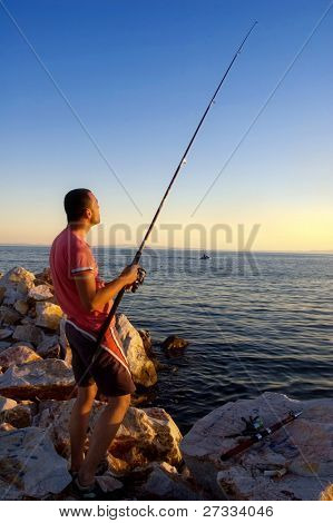 Fisherman catching fish with a fishing pole during sunset