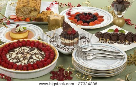 Elegant table with many desserts and fruits (eclair, pecan swirl cake, raspberry pie, rice pudding, cheese cake, creme caramel, and more)