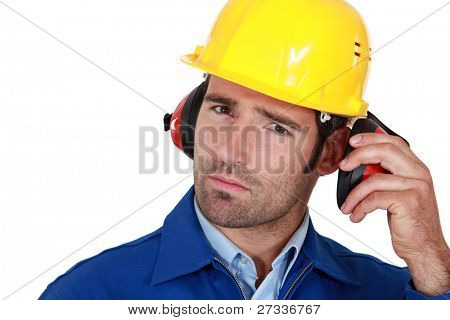 Man wearing safety earmuffs and helmet