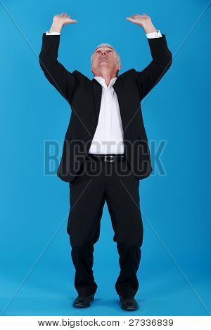 A businessman raising his hands to the sky.
