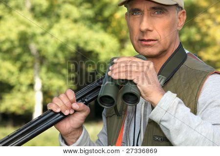 Hunter with a shotgun and pair of binoculars