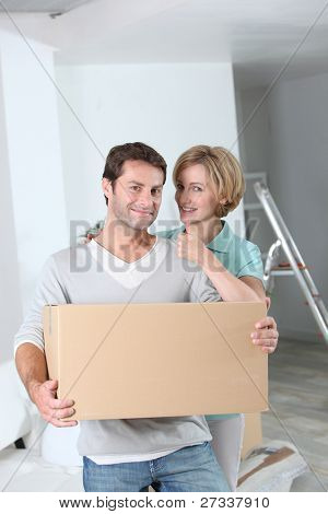 Woman giving the thumbs up to her partner as they move into a new home