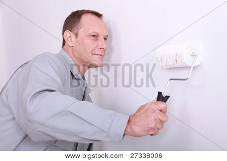Decorator painting a wall white