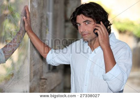 Man on telephone looking at map for directions