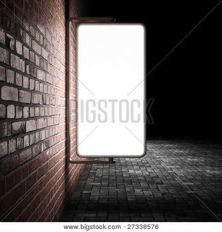 Blank street advertising billboard on brick wall at night