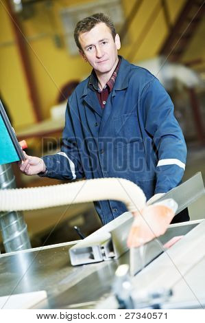 mechanical technician worker with circ saw machine at wood furniture manufacturing workshop