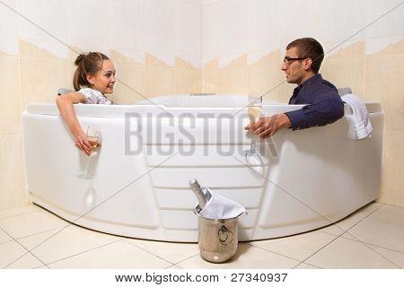 ein junge schöne Paar genießen Sie ein Bad mit Sekt in einem Glas und Blick auf einander