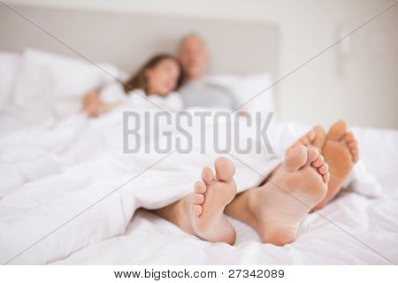 Lovely couple lying in a bed with the camera focus on their feed