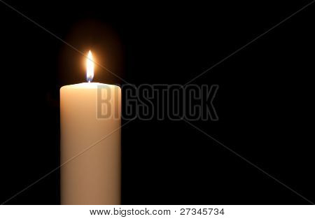 White Candle Isolated Against A Black Background