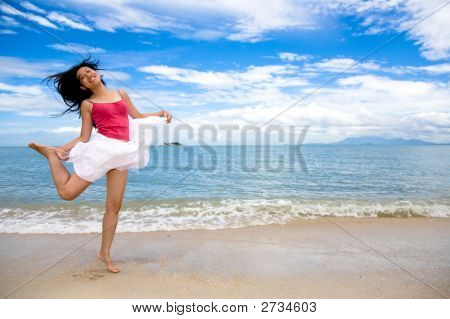 Young Woman Jumping Playfully At The Beach