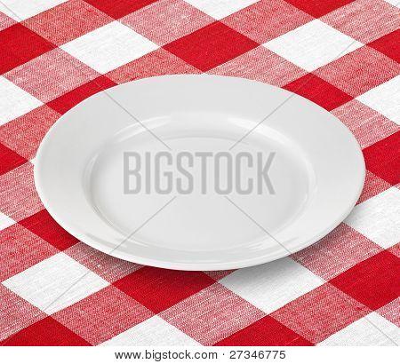 weiße leere Platte auf rot karierte Tischdecke