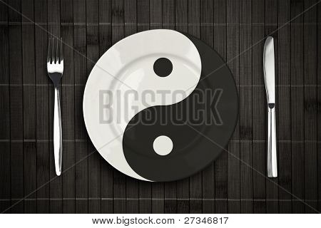 yin yan plate over bamboo placemat setting with fork and knife