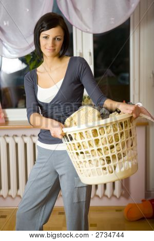 Woman With Laundry Basket In House