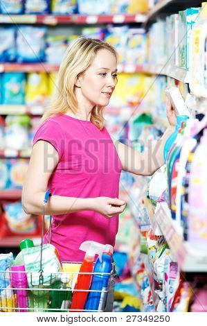 woman choosing household chemistry produces in shopping mall
