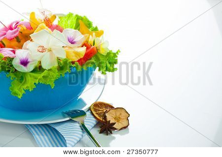 Fruit Salad With Edible Flowers In A Blue Bowl From Ice On White Background