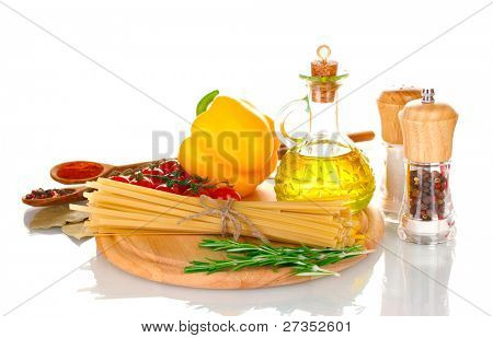 spaghetti, jar of oil, spices and vegetables on wooden board isolated on white