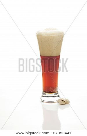 Dark  Beer With The Foam In A Tall Glass And Pistachios Isolated On White