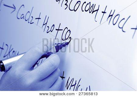 Hand writes a chemical formula on a chalkboard,Closeup.