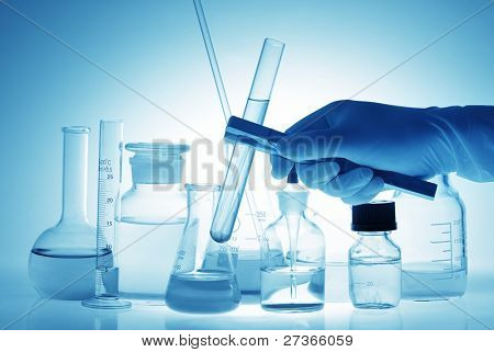 Scientific (or Medical) Experiment--Scientist holding tube in front experiment bottles.