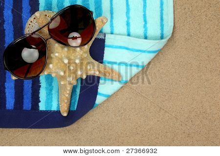 Colorful summer beachwear, sunglasses, starfish and towel  on sand beach.