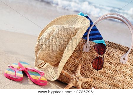 Closeup of summer beach bag with items on sandy beach