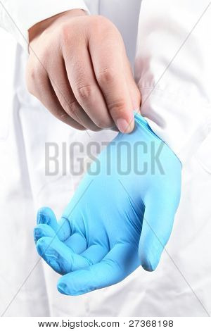 Doctor putting on blue sterilized medical glove for making operation
