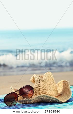 Concept of summer holidays with straw hat and sunglasses on sandy beach