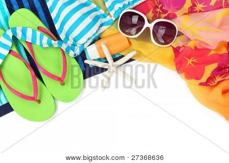 Beach accessories with swimming suit,sun glasses,shawl and flip flops on white background.
