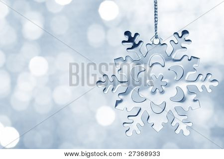 Silver blue snowflake against shimmering background