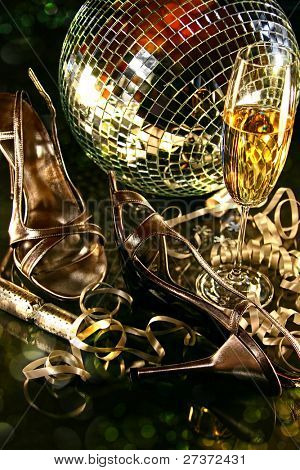 Silver party shoes on floor with champagne glass for New Year's Eve