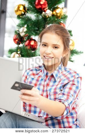 happy woman with laptop computer and credit card over christmas tree