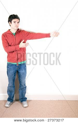 Brunette guy pointing to copy space to his left.