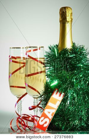 Two champagne flutes with green tinsel, bottle of champagne and sale tag near by