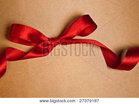 Shiny red satin ribbon on golden background with copy space