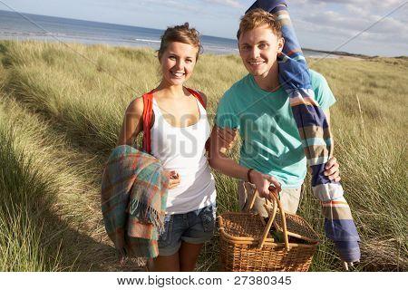 Young Couple Carrying Picnic Basket And Windbreak Walking Through Dunes