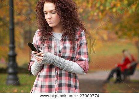 Frustrated Teenage Girl Making Mobile Phone Call In Autumn Landscape