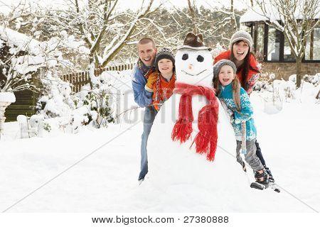 Family Building Snowman In Garden