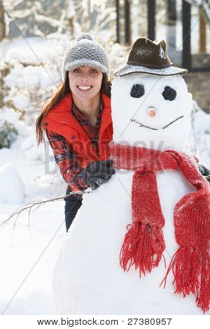 Young Woman Building Snowman In Garden