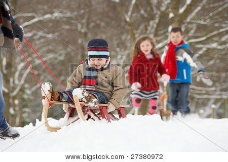 Padre de retirar a los niños en trineo a través del paisaje de invierno