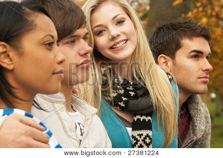 Close Up Of Group Of Four Teenage Friends In Autumn Woodland
