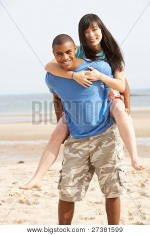 Young Couple Having Piggyback Fun On Beach