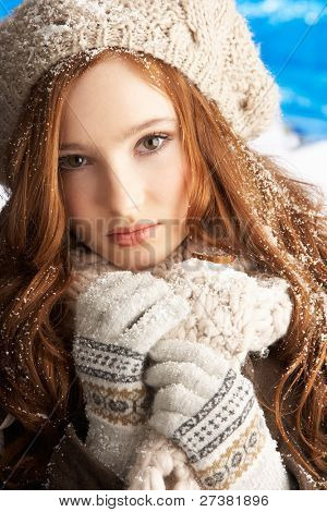 Teenage Girl Wearing Warm Winter Clothes And Hat In Studio