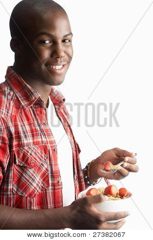 Young Man Eating Bowl Of Healthy Breakfast Cereal In Studio