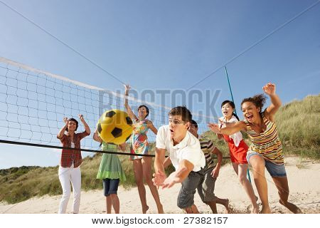 Grupo de amigos adolescentes jogando vôlei na praia