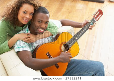 Young Couple Relaxing Sitting On Sofa Playing Acoustic Guitar