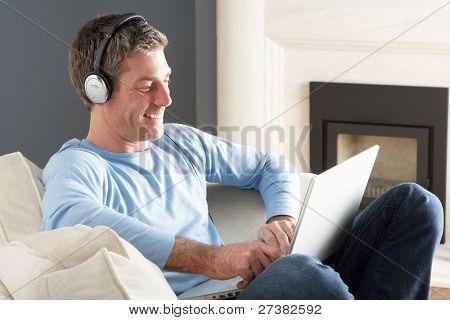 Mann mit Laptop tragen von Kopfhörern entspannten sitzen auf dem Sofa zu Hause